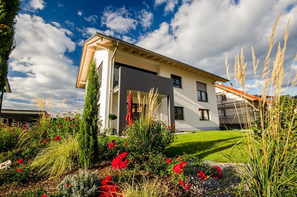 Modernes Haus mit Wiese und Blumen.