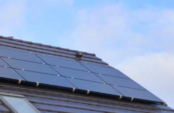 Schwarze Photovoltaikmodule auf glatten Dachpfannen vor sonnigem Himmel