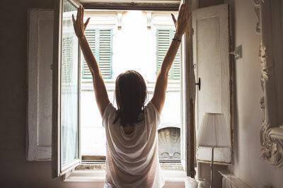 Eine Frau macht das Fenster auf und lässt die Sonne herein